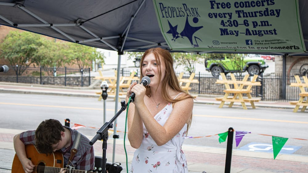 Olivia Doyle sings as Derrick Weidner plays the guitar at Peoples  Park on May 27. Musical duo Carnes & Shew will perform a free concert at People's Park on Thursday night.