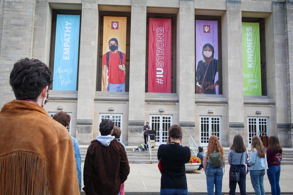 <p>Rallygoers stand in front of the IU Auditorium on Friday afternoon. Students organized to call for IU to fire associate professor Murray McGibbon, but IU confirmed McGibbon resigned shortly before the rally began.</p>