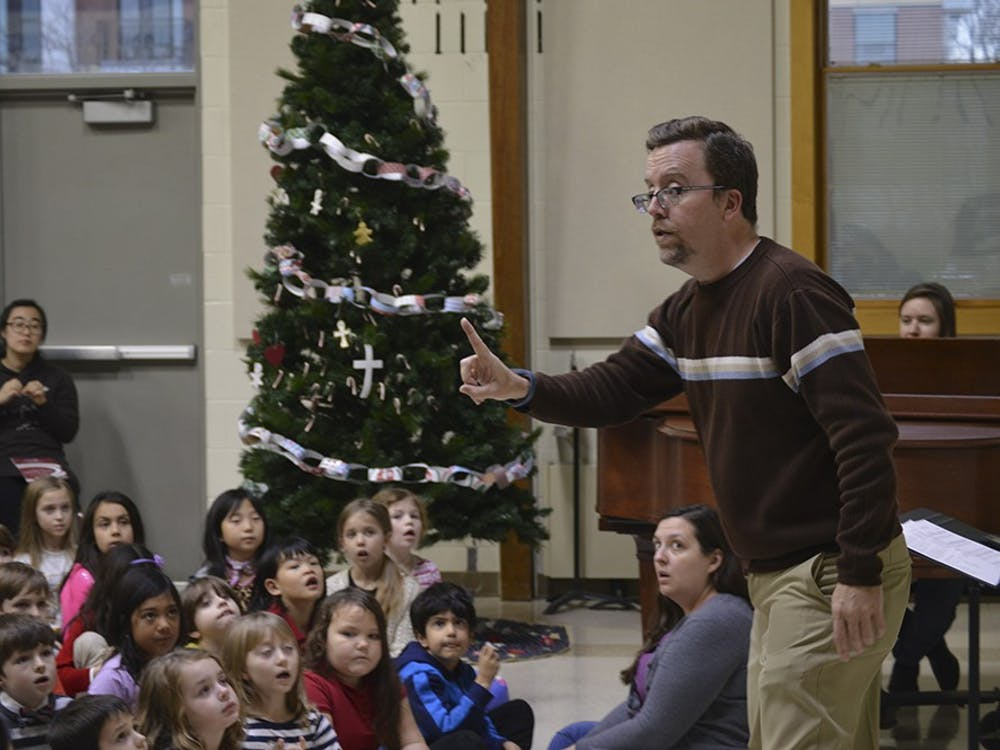 Etienne Lamb (left) and Story Bolton watch the IU Children's Choir director as they rehearse for the program's Winter Concert. The performance will feature a mixture of Christmas, Hanukkah and secular songs, and it begins at 1 p.m. Saturday at St. John the Apostle Church.