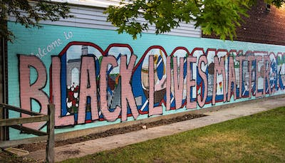 """Lights shine July 13 on the mural in Peoples Park. """"Black lives matter"""" was painted over the mural following the killing of George Floyd by Minneapolis police in May."""