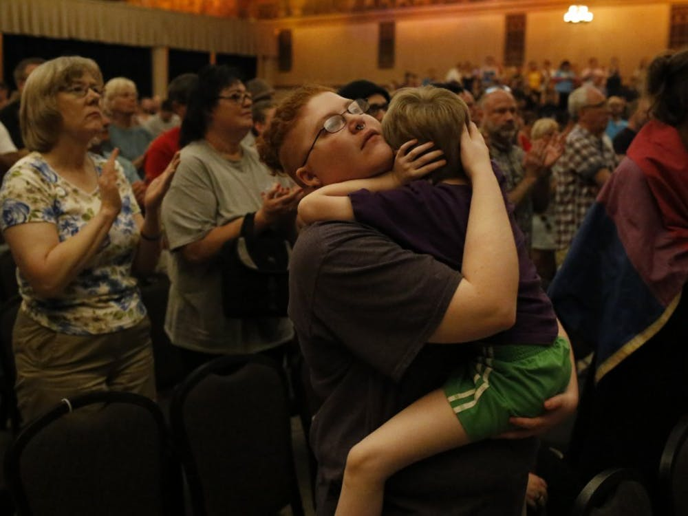 """Sebastian Calhoun holds his 6 year old son during a vigil, which took place in the Egyptian Room at the Old National Centre Sunday evening and was sponsored by Indy Pride in response to the recent mass shooting that took place at a gay night club in Orlando, Florida. """"I came here for Solidarity,"""" he said."""