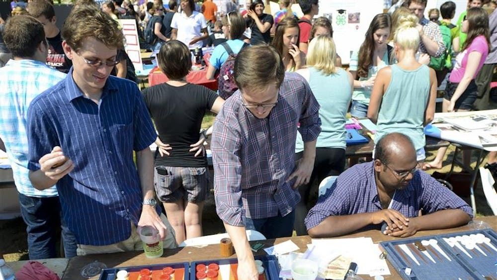 Members of the backgammon club, graduate students Erik Wallace, Brian Rogers and Neeraj Kashyap play backgammon at the Student Involvement Fair on Wednesday in Dunn Meadow.