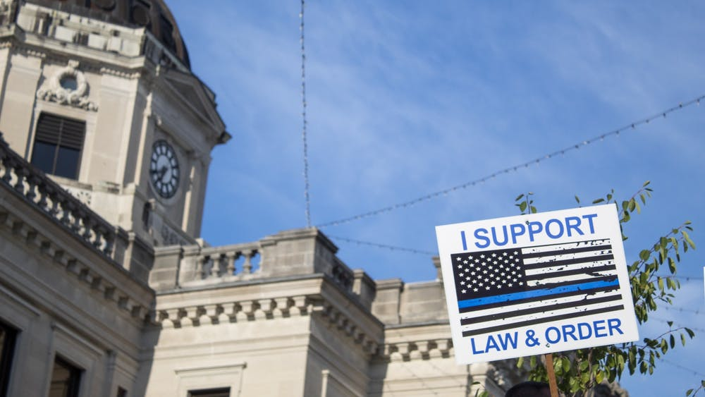 "A sign reading ""I support law & order"" is held up Aug. 22 in front of the Monroe County Courthouse. During the protest there were several altercations between pro-police and Black Lives Matter groups."