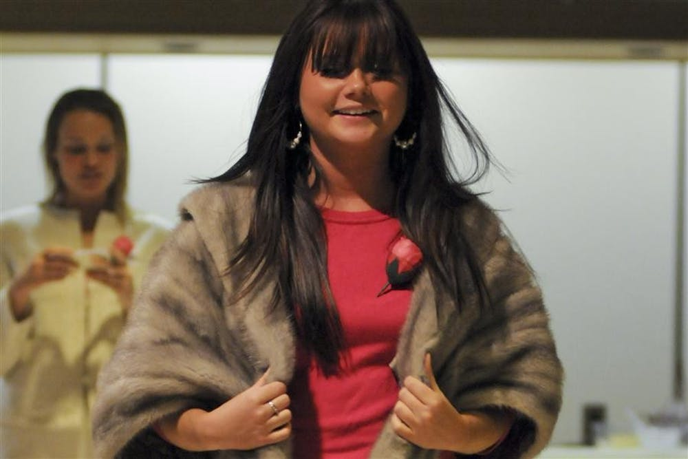 A student model in My Sister's Closet appearel walk down the runway in Briscoe Formal Lounge Monday. My Sister's Closet  provides professional clothing and accessories free to women who qualify and at affordable prices to the general public. The Bloomington store is located at 1010 S. Walnut St.