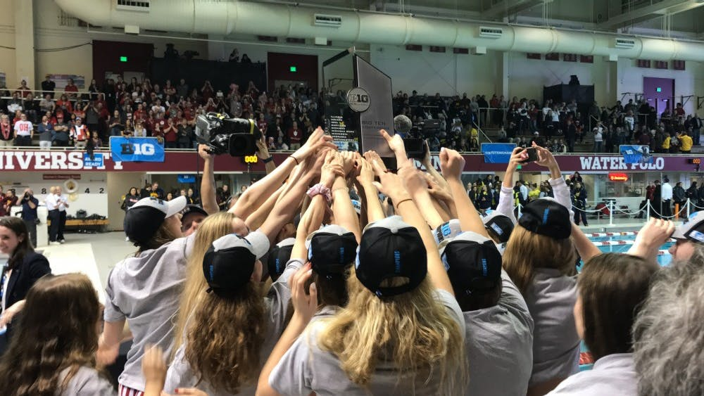 The IU women's swim and dive team lifts the Big Ten Championship trophy Feb. 23 after winning the team title. This was the team's first Big Ten title since 2011
