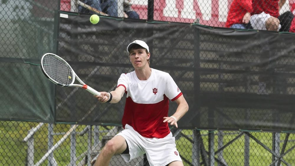 IU graduate student Bennett Crane prepares to hit the ball in a match against Nebraska on Feb. 21. The Hoosiers defeated Purdue 4-0 on Saturday at the IU Tennis Center.