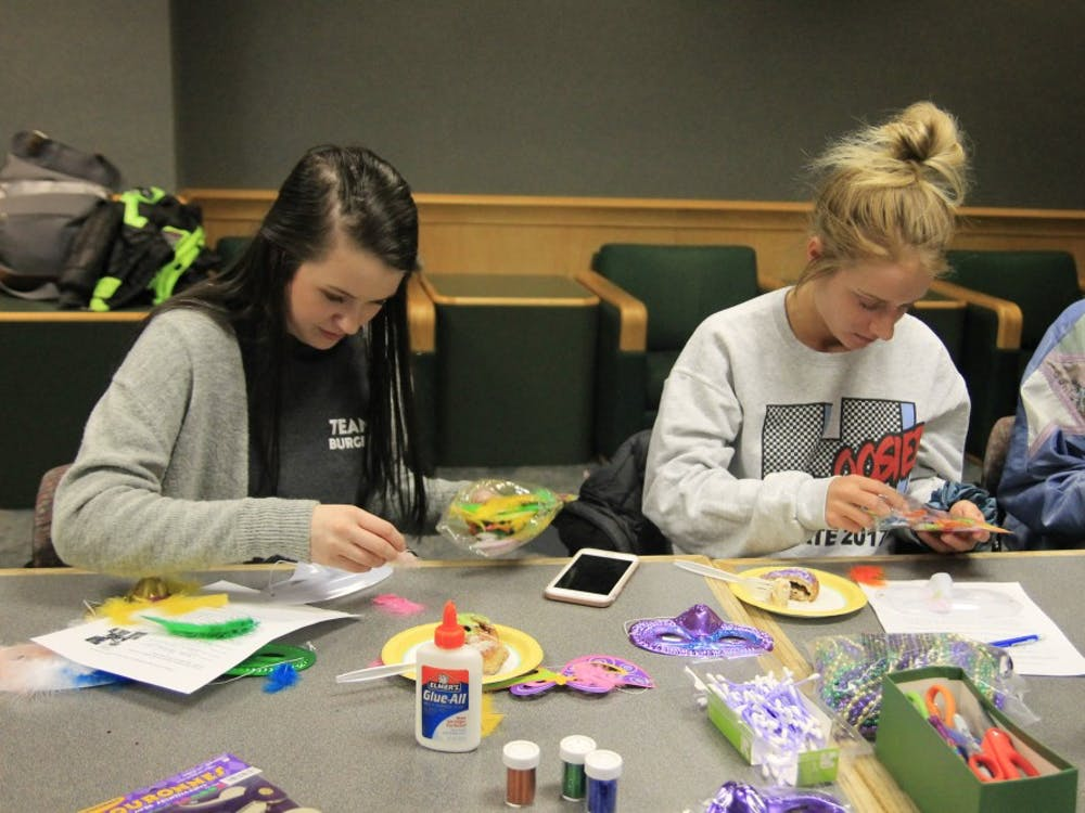 Freshman roommates Lauren VanderReyden and Rylea James make masks as a Mardi Gras tradition. The French Club and classes celebrated Mardi Gras on Tuesday, Feb. 13, in Ballantine Hall.