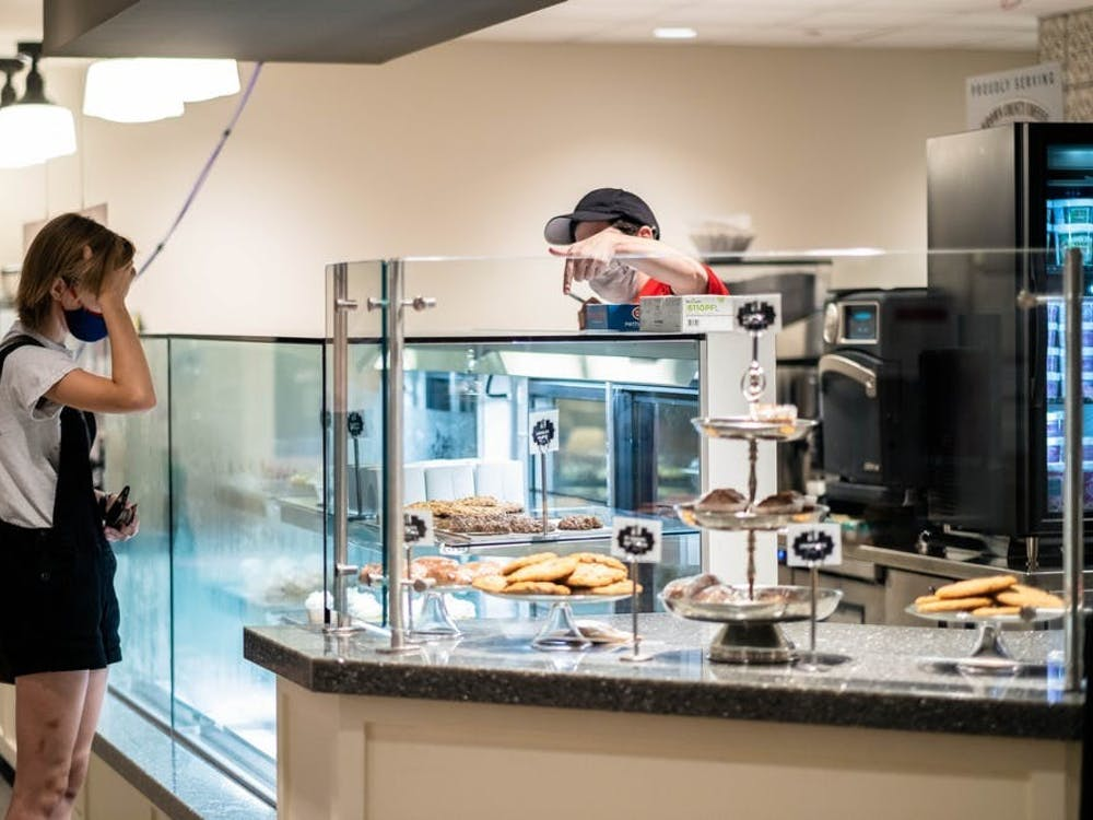An Indiana Memorial Union dining staff employee serves a customer at Sugar and Spice in the IMU. The IMU will open four new restaurants Monday.