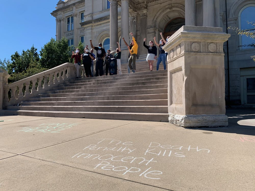 """Protesters lead a song during the """"Does DNA Evidence Matter?"""" rally Sept. 20 at the Vigo County Courthouse in Terre Haute, Indiana. The chalk in front of the stairs reads, """"The death penalty kills innocent people."""""""