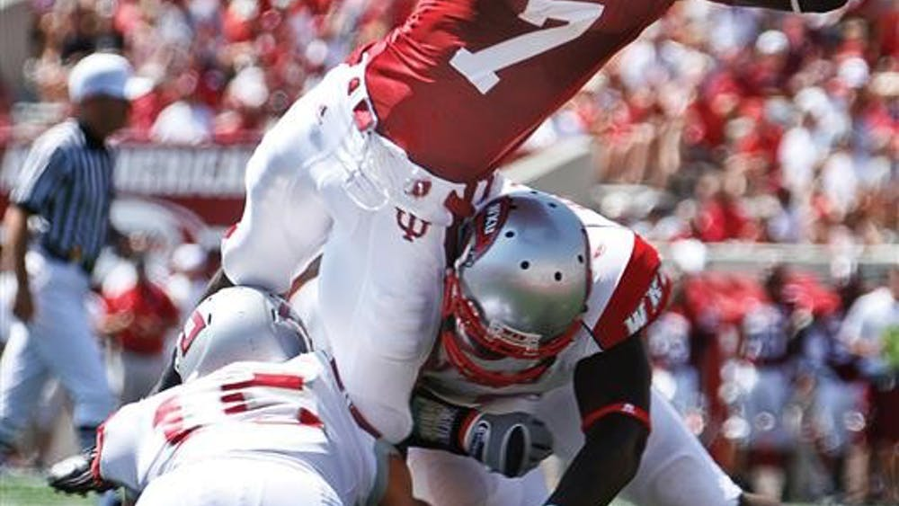 Junior wide receiver Ray Fisher leaps into the end zone over two Western Kentucky defenders during the Hoosiers' 31-13 win against the Hilltoppers Saturday at Memorial Stadium.