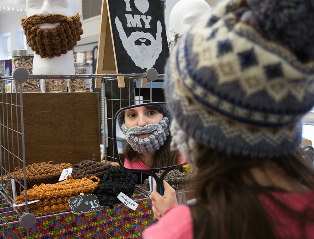Senior Jennifer Smith trys on a handmade crochet beard by Jo Designs at the Bloomington Handmade Market on Saturday.