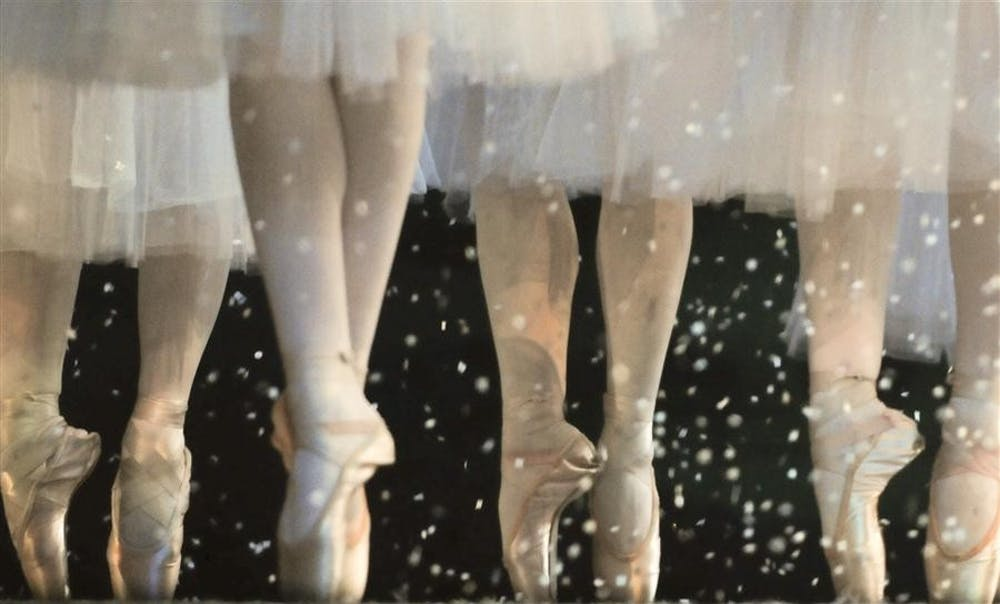 """<p>Dancers in the snow scene of """"The Nutcracker"""" balance on pointe during a rehearsal Dec. 2, 2010&nbsp;at the MAC.</p>"""