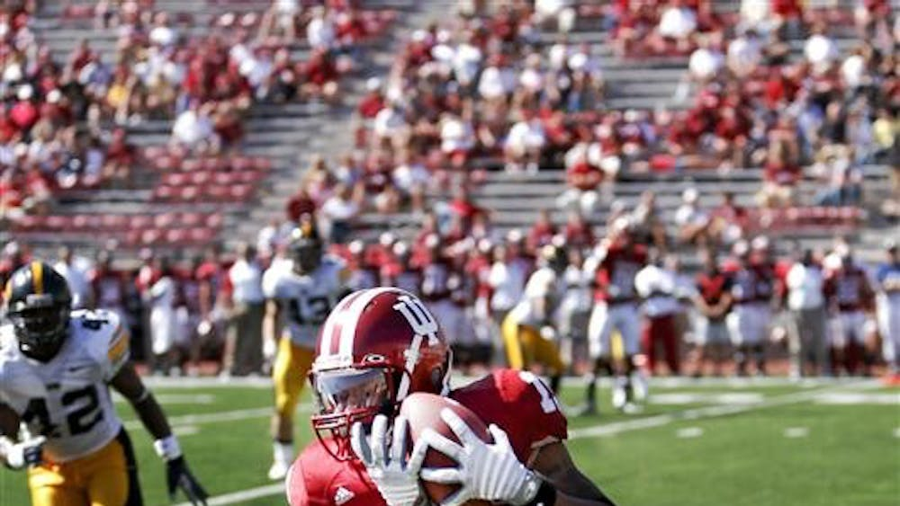 Senior wide receiver Brandon Walker-Roby takes a hit from Iowa defensive back Amari Spievey in front of a thinning Memorial Stadium crowd during the Hoosiers 45-9 loss to Iowa Saturday afternoon at Memorial Stadium.