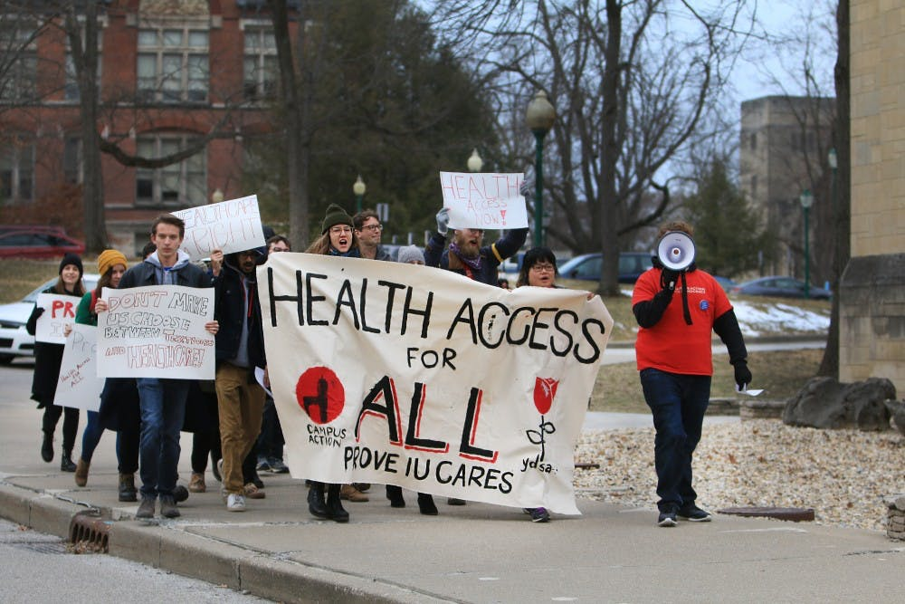 <p>Students march through campus March 7 carrying a sign stating, &quot;Health access for all.&quot; Students rallied outside IU President Michael McRobbie&#x27;s office to bring attention to improving health care at IU. </p>