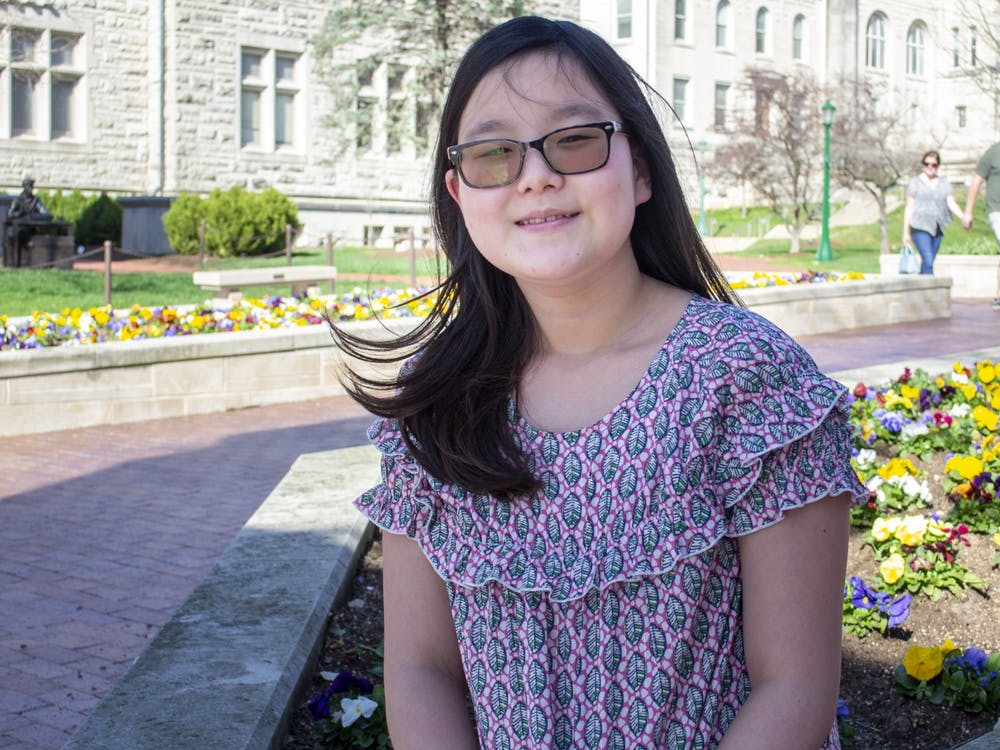 Sixth grade student Yena Park sits March 30 by the Sample Gates. Park has won the IU spelling bee three years in a row.