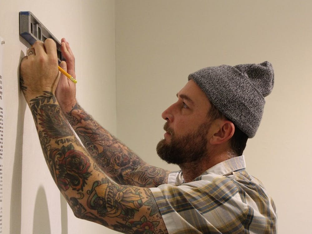 Exhibit curator Jeremy Sweet marks a spot to hang a print in the Grunwald Gallery. Sweet co-curated an exhibit, which will open Friday, focusing on the history and legacy of Indiana tattoos.
