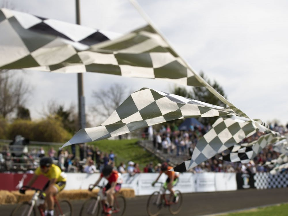 Flags wave in the breeze in front of riders competing in the 2019 women's Little 500 race April 12 at the Bill Armstrong Stadium. The riders biked 100 laps to the sounds of a raucous, supportive crowd.