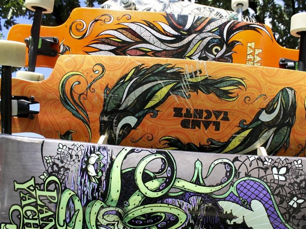 Landyachtz Longboards sit on a display rack in Dunn Meadow. Representatives from the Vancouver-based company visited Bloomington on Tuesday to inform students about their business during a promotional tour.