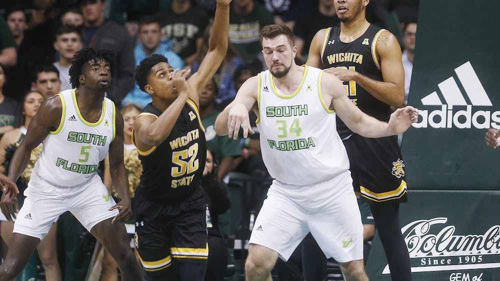 Wichita State University's Grant Sherfield and University of South Florida's Antun Maricevic battle for a rebound during the first half Jan. 21 at the Yuengling Center in Tampa, Florida. Adding a salary cap to NCAA athletics would mean each program would have a gap on how much money it can spend on its rosters.