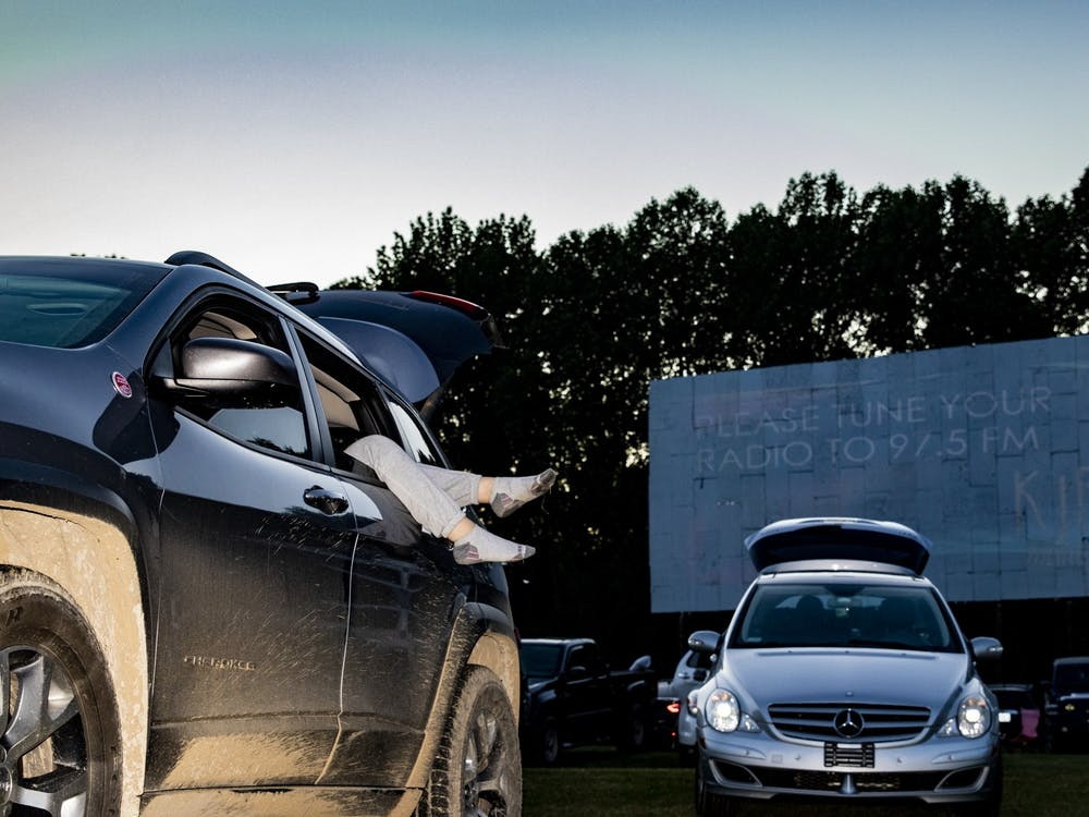 """Feet dangle outside of a car window May 22 at the Starlite Drive-In Theater. """"Please tune your radio to 97.5 FM,"""" the big screen reads, to inform moviegoers on how to listen to the audio for """"Trolls: World Tour"""" and """"Dolittle."""""""