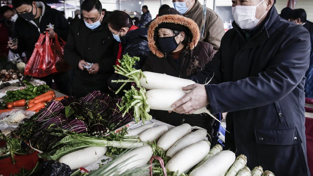 Chinese residents wear masks to buy vegetables Jan. 23 at a market in Wuhan, Hubei.