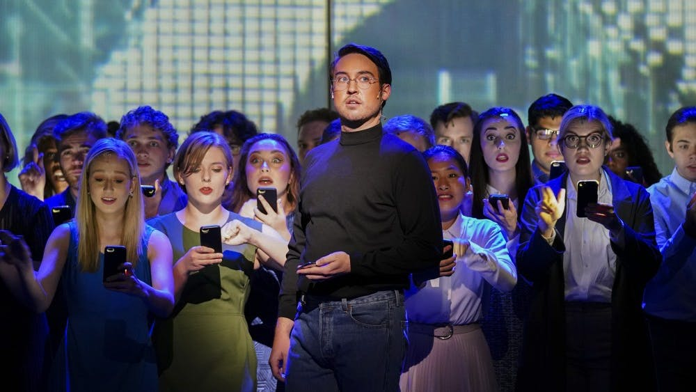 "A mob of smartphone users grows behind Steve Jobs, portrayed by Edward Cleary, as the cult following of Apple products is depicted during the ""(R)evolution of Steve Jobs"" rehearsal Sept. 11 in the Musical Arts Center. The opera tells the story of the life and death of Apple co-founder Steve Jobs."