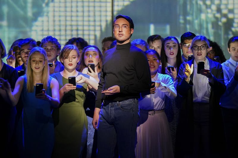 """A mob of smartphone users grows behind Steve Jobs, portrayed by Edward Cleary, as the cult following of Apple products is depicted during the """"(R)evolution of Steve Jobs"""" rehearsal Sept. 11 in the Musical Arts Center. The opera tells the story of the life and death of Apple co-founder Steve Jobs."""
