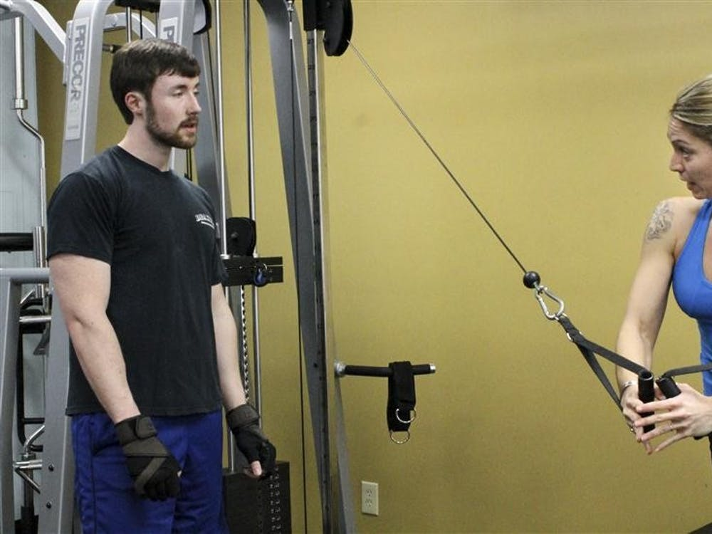 Clay Aschliman watches as Anytime Fitness trainer Meredith Allyn demonstrates a chest exercise on Jan. 11 at the gym. Aschliman, 27, said his New Year's fitness resolution is to gain size and strength.