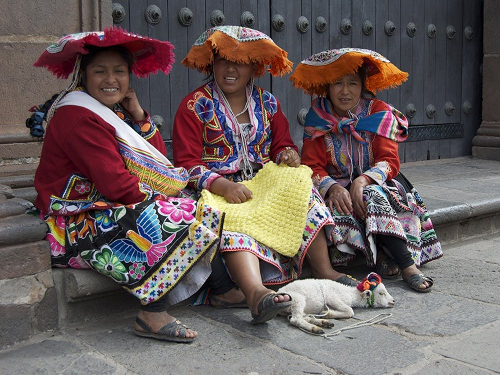 Women in traditional clothes sit on one of the streets of Cuzco with a lamb, allowing passing visitors to pet it and hold it for a couple soles, the Peruvian currency.