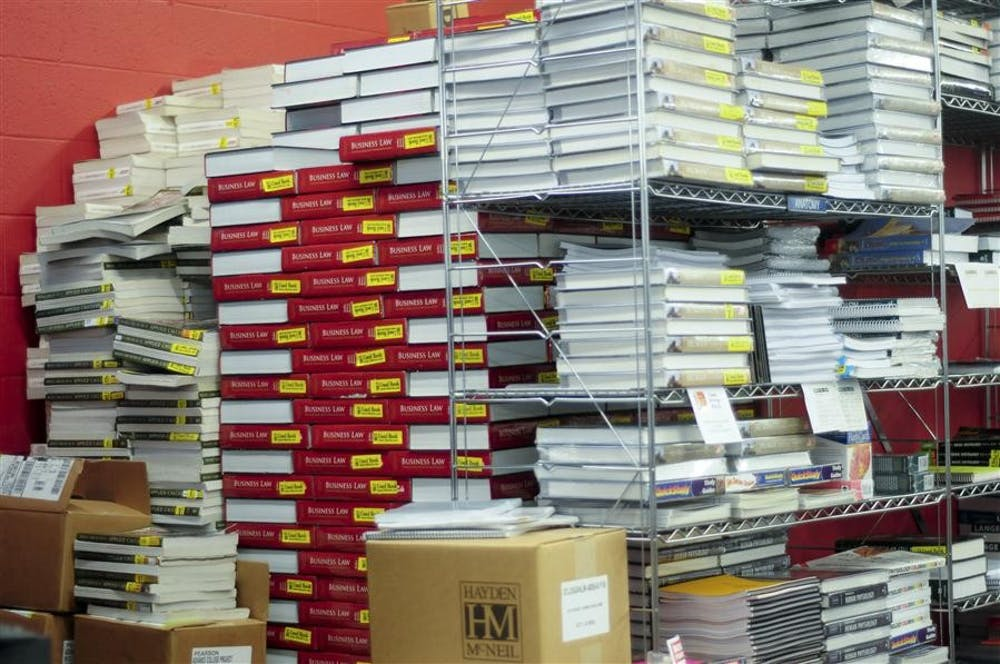 <p>Finite, Applied Calculus, and Business Law textbooks are stacked in a giant pile in the upstairs textbook section of TIS College Bookstore. </p>