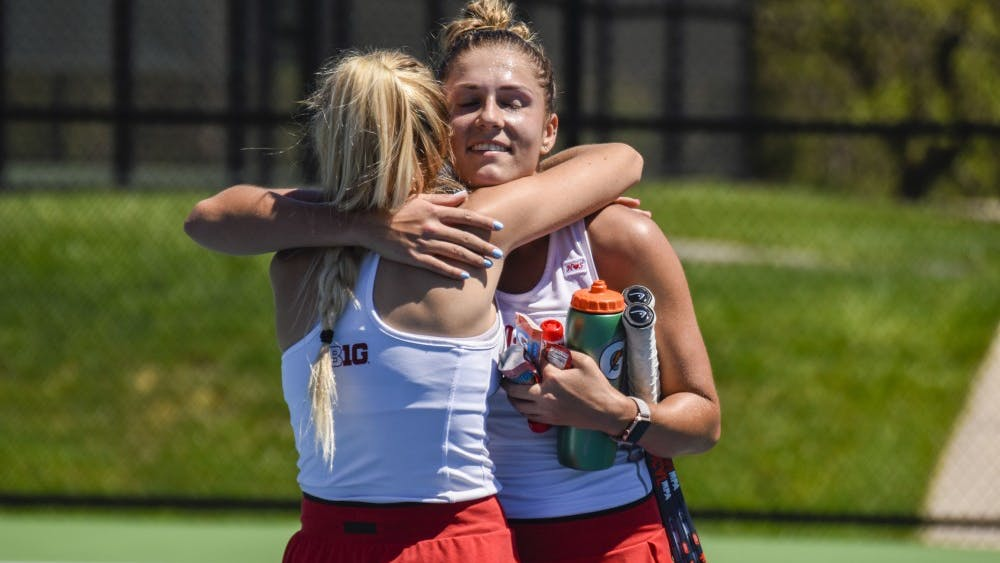 Seniors Madison Appel, left, and Natalie Whalen, right, hug after Whalen won her singles match against Maryland on April 21 in Bloomington. IU won all six singles points in its 6-1 win over Maryland.