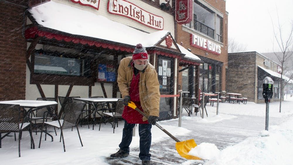 Nick's English Hut General Manager Pete Mikolaitis shovels snow from the sidewalk Monday on Kirkwood Avenue. Bloomington is expected to receive as much as a foot of snow between Monday afternoon and Tuesday morning.