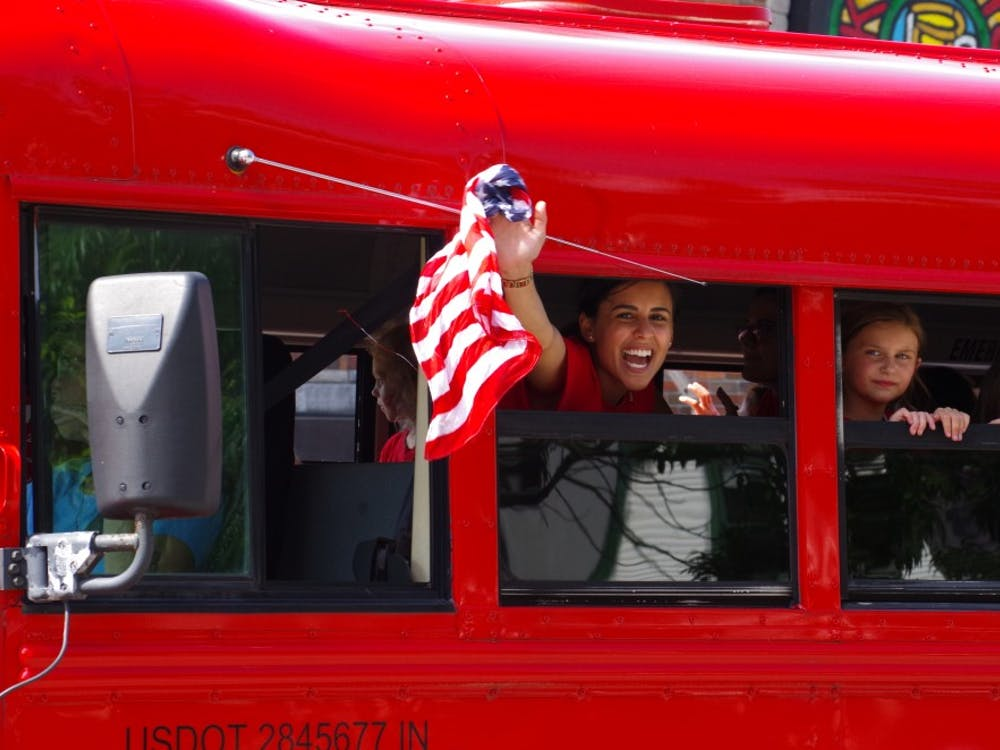 Members of the local Girls Inc. of Monroe County wave and yell out the window of their red bus at those watching the Bloomington Fourth of July Parade. Girls Inc. is a nonprofit dedicated to helping young girls overcome stereotypes.