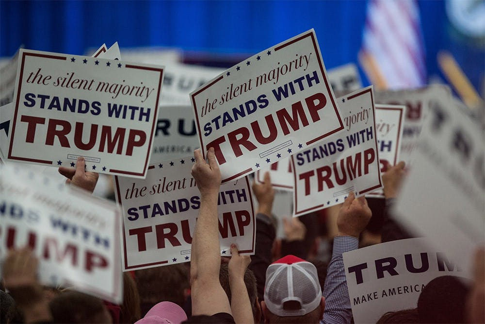 Supporters of presidential candidate Donald Trump hold signs up as Trump walks on stage to speak at a rally at the Kentucky International Convention Center in Louisville, Kentucky on Tuesday.