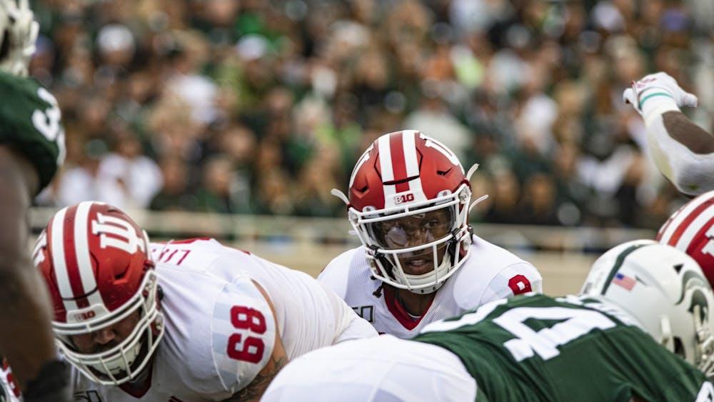 Then-redshirt freshman quarterback Michael Penix Jr. peers over Michigan State University's defensive linemen Sept. 28, 2019, in Spartan Stadium. Indiana will play Michigan State on Saturday.