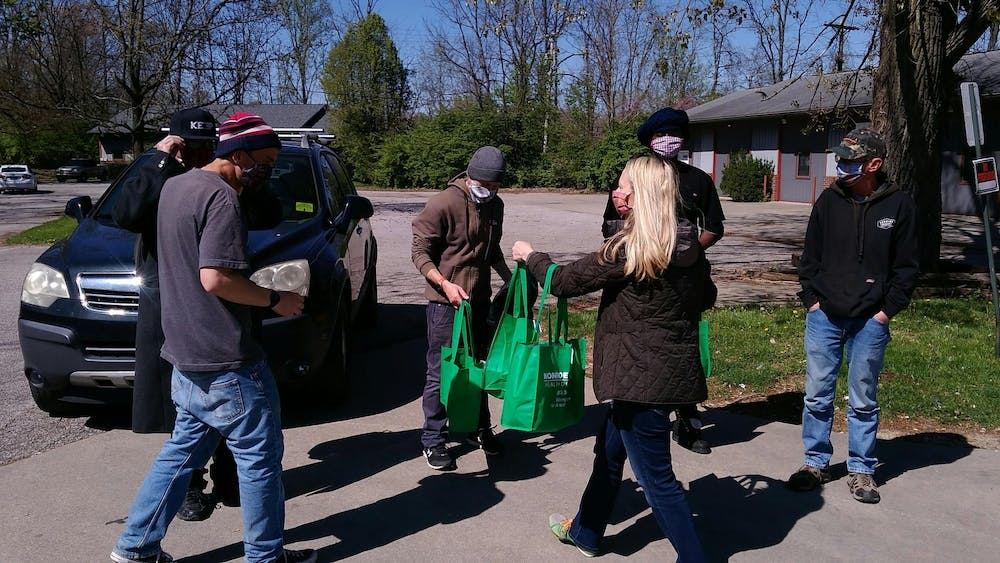 <p>Community members distribute sanitation kits as part of the Monroe County Health Department&#x27;s partnership with Wheeler Mission. The kits include a bandana, hand sanitizer and an informational card on how to lessen the spread of the coronavirus.</p>