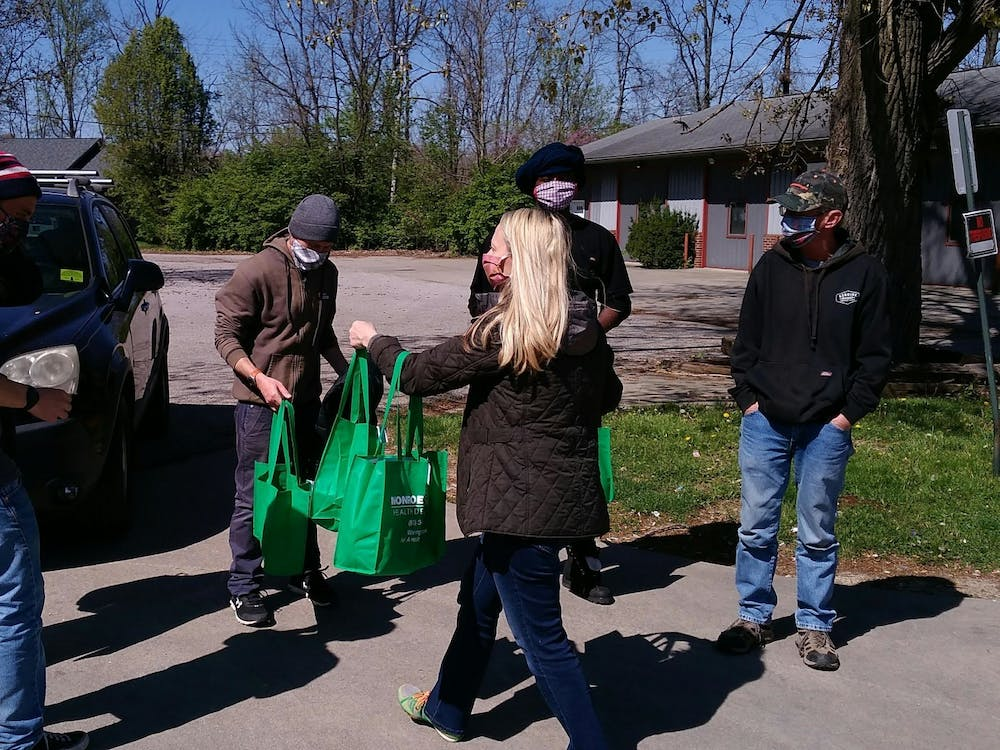 Community members distribute sanitation kits as part of the Monroe County Health Department's partnership with Wheeler Mission. The kits include a bandana, hand sanitizer and an informational card on how to lessen the spread of the coronavirus.