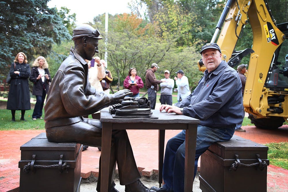 Sculptor Tuck Langland sits with the sculpture of Ernie Pyle he created for The Media School on Thursday outside Franklin Hall. There will be a dedication of the Ernie Pyle sculpture on Oct. 17, along with a formal inauguration of The Media School.