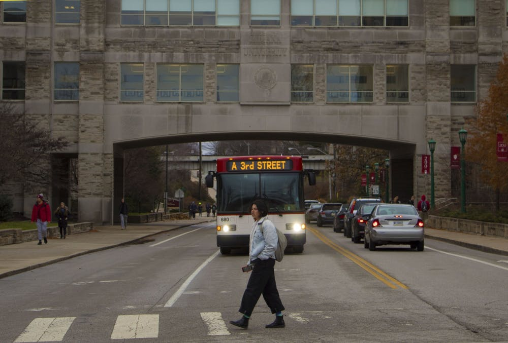 <p>A student walks in front of the A bus on Dec. 2, 2019, in front of the Kelley School of Business.</p>