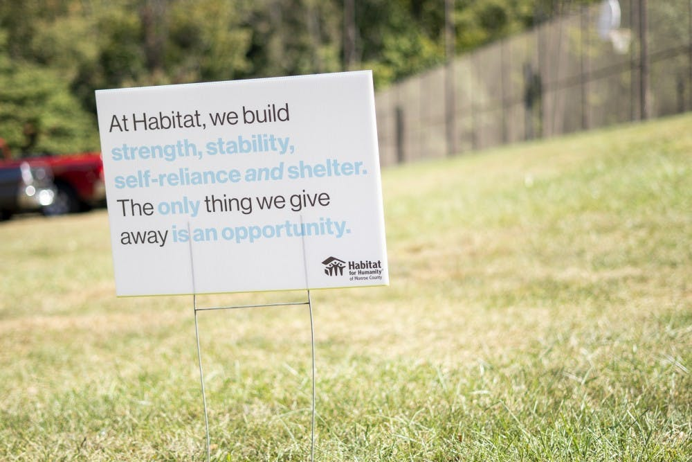 <p>A signs sits in front of the Habitat for Humanity site Oct. 9 on North Fee Lane. Signs lined the street, explaining the organization's purpose and sponsors. </p>