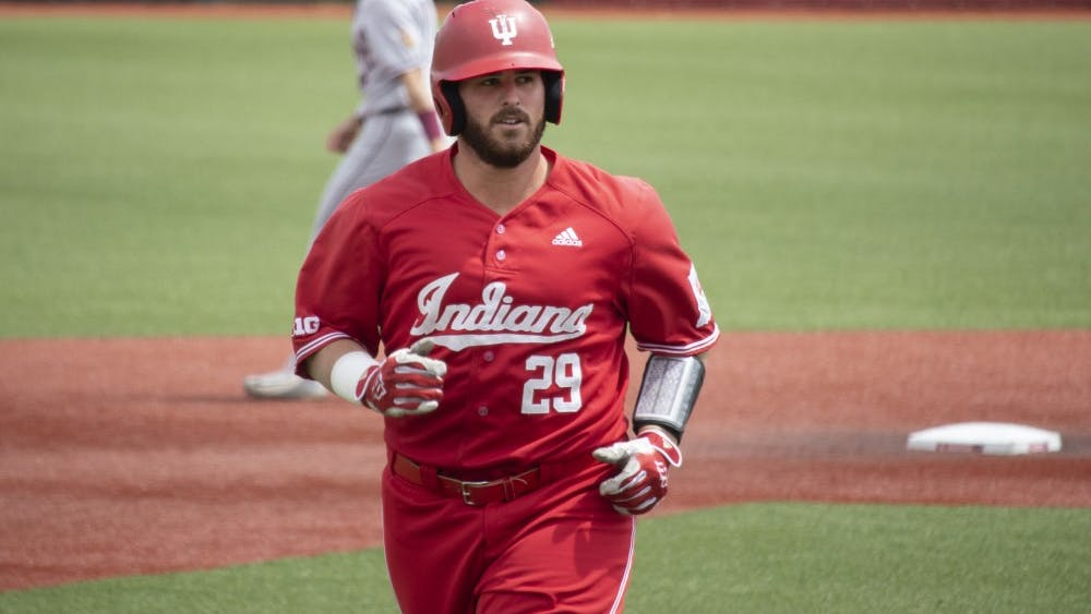 Senior catcher Ryan Fineman runs back to the dugout Sunday at Bart Kaufman Field. Fineman hit a fly ball out to right field, and it was caught at the bottom of the third inning against Minnesota.