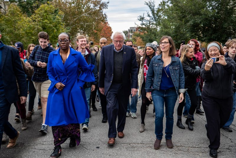 Sen. Bernie Sanders, I-Vermont, center, walks with Liz Watson, center right, down Indiana Avenue to lead a group of people to a voting center in Bloomington on Oct. 19 after Sanders and Watson spoke at a rally at Dunn Meadow.