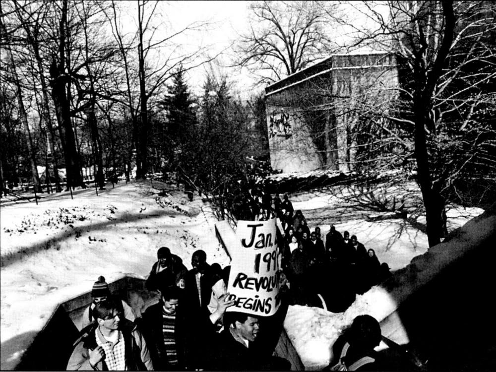 """Senior Glenn Murphy holds up a sign Jan. 20, Martin Luther King Jr. Day, that reads, """"Jan. 20, 1997 The Revolution Begins."""" An estimated 400 protesters marched by Ballantine Hall and chanted, """"The students united, will never be defeated."""" Bruce Smail, interim director of the LGBTQ+ Culture Center, was part of the Student Coalition when he was a graduate student at IU."""