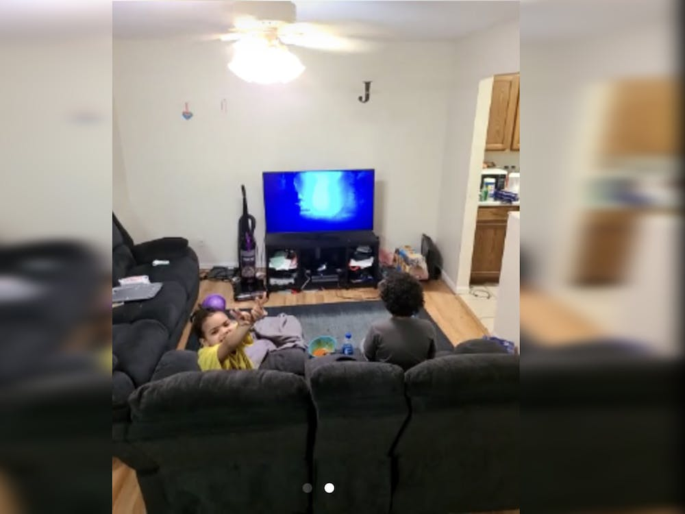Raelynne Wilson, 6, and Matthew Woods, 9, sit in the living room at the end of the day. Matthew is playing video games.