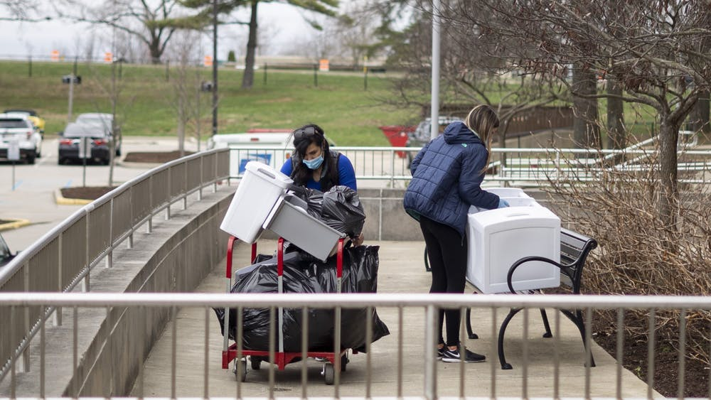 Two women bring out multiple items from Tulip Tree Apartments on March 20 during the coronavirus pandemic.