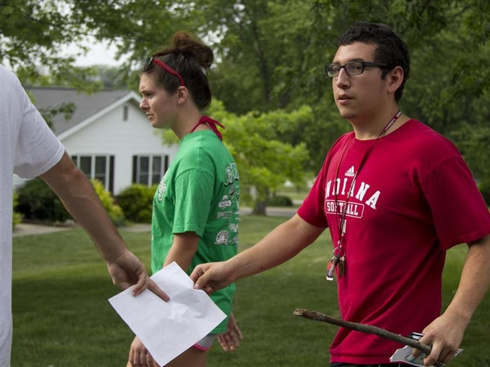 Senior Bryan Guadango hands senior Xavier Medina the map of their designated search area as senior Valerie Theobald walks alongside the men Friday on  E. Waterloo Court during their search for Lauren Spierer.
