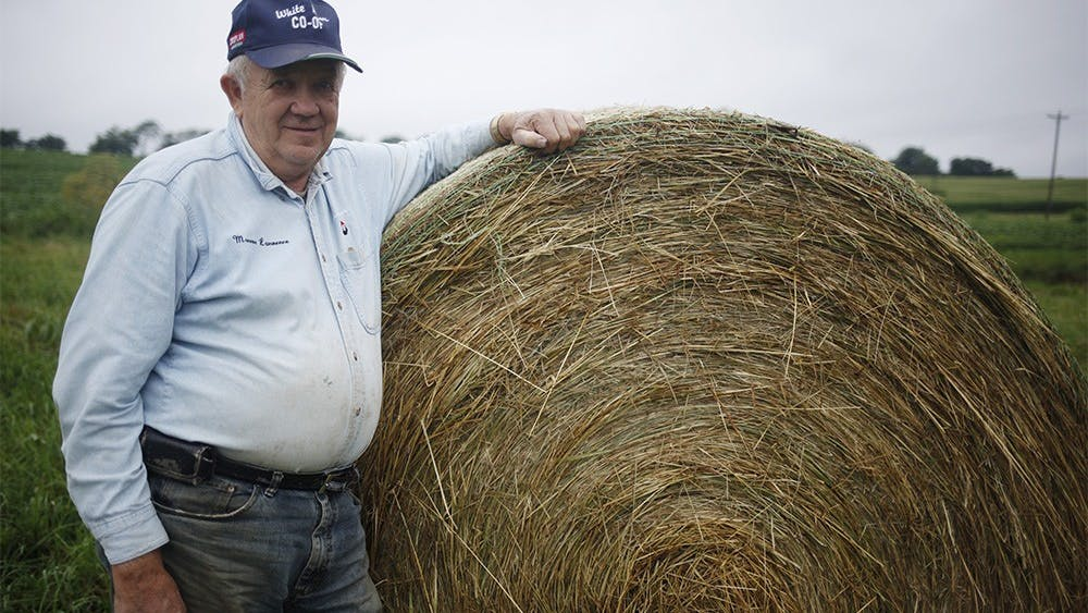 Joe Peden poses in front of a bale of hay on his property July 8, 2015, at Peden Farm in Bloomington. Peden is one of many farmers struggling to produce crops this year due to excessive rainfall.