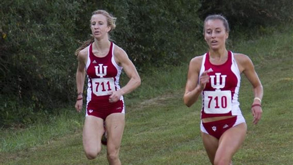 Senior Samantha Ginther runs with junior Kelsey Duerksen during the Indiana Open on Sept. 7 at the IU Cross Country Course. Ginther finished second in the race.