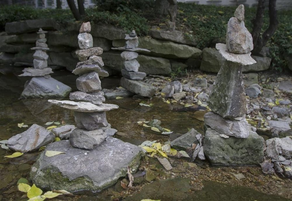 Rock sculptures line the Jordan river near Franklin Hall. Over the last week, Patrick Siney has been lining the river with these rock sculptures as an independant art project after becoming inspired by something similar he saw in Colorado. Other Bloomington residents and students have also  contributed to the sculpture building.