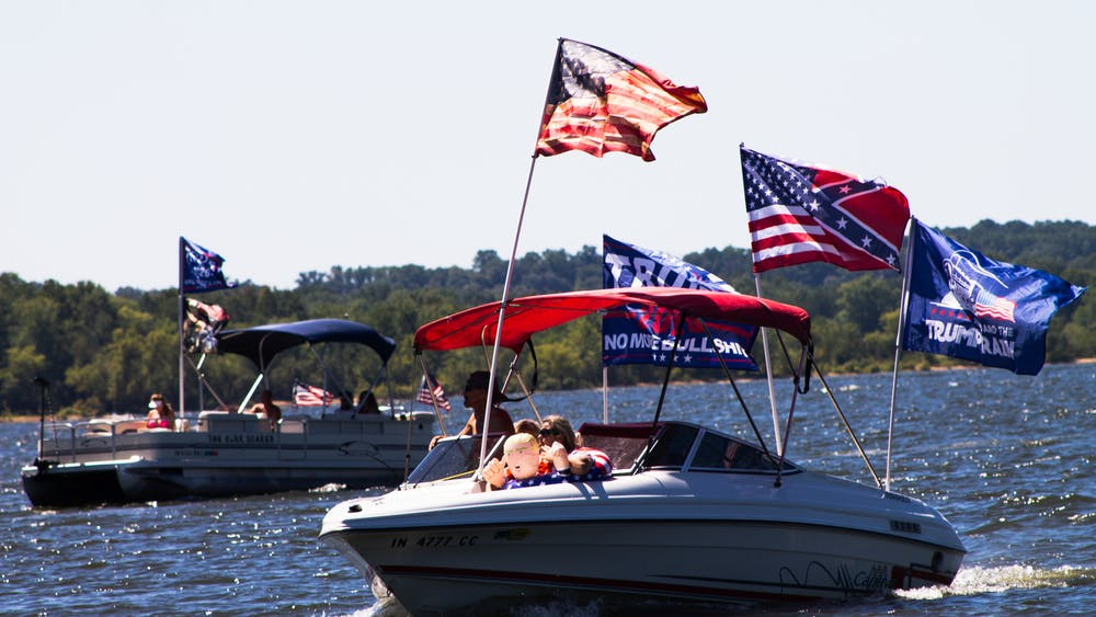 A boat with flags displaying support for President Donald Trump's reelection campaign and the confederate flag drives Saturday for a boat parade on Monroe Lake. The parade was one of hundreds across the country over the weekend.